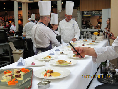 a very small sample of work going on in the kitchen, scrutinised by the members of the judging panel.